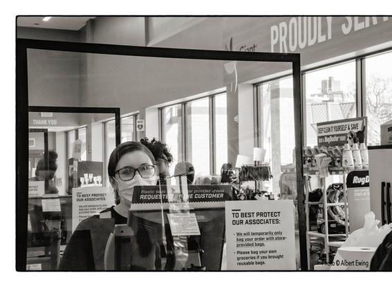Grocery Store Employee Wearing Mask Behind PlexiGlass