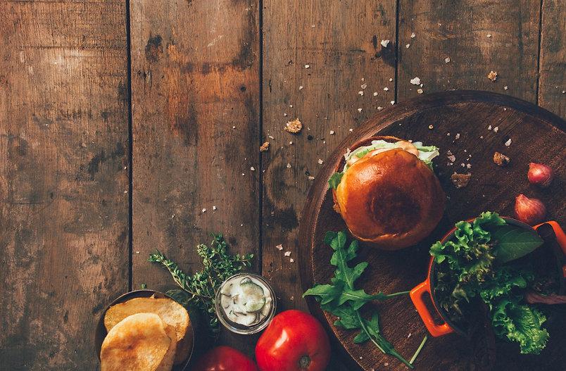 Burger mit frischem Salat und Tomaten auf einem Holztisch