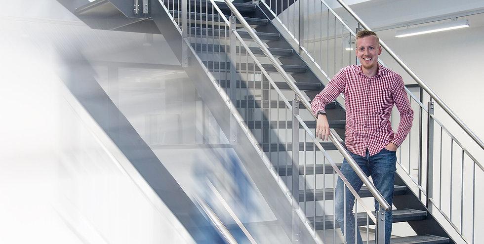 Mitarbeiter der Firma steht lächelnd auf einer Treppe in der Firma