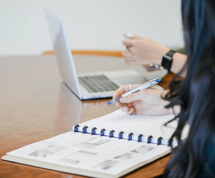 EIn Schreibtisch mit einem Laptop und Notizbuch, zwei Menschen arbeiten daran