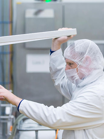 MItarbeiter in hygienischer Arbeitskleidung an einer Produktionsmaschine