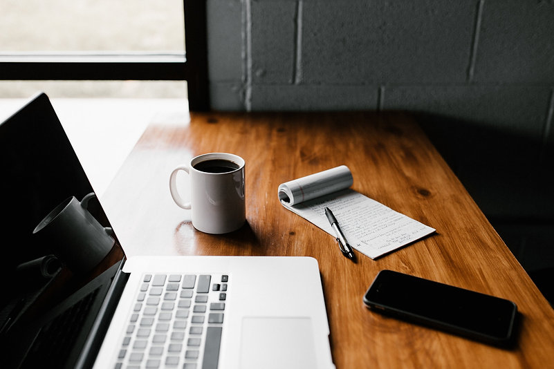 Schreibtisch mit Laptop, Notizblock, Kaffeetasse und Smartphone