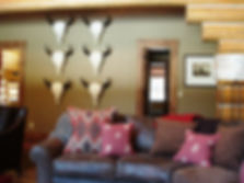 CADENET DESIGN AND ASID DESIGNER ROBIN CHRISTENSEN, CREATED BISON SKULL WALL, CUSTOM UPHOLSTERY HORSESHOE SHAPED SOFA AND CUSTOM PILLOWS ON JACKSON WYOMING LOG HOME