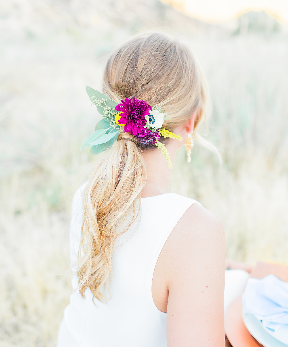 Bridal hair with burgundy, yellow, and white flowers.