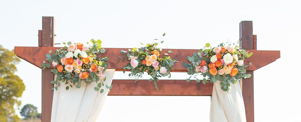 Orange and peach wedding altar flowers at Peacock Gap Golf Club in Novato, California