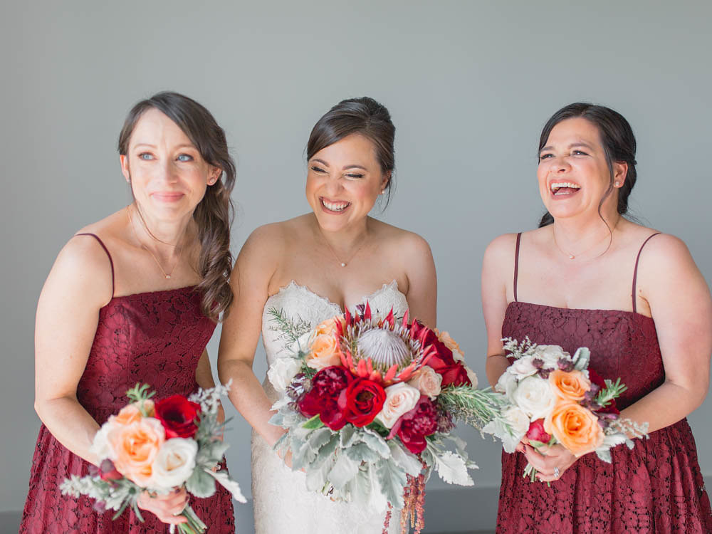 Burgundy, Peach, Red, and Blush wedding bouquets. A bride and her bridesmaids.