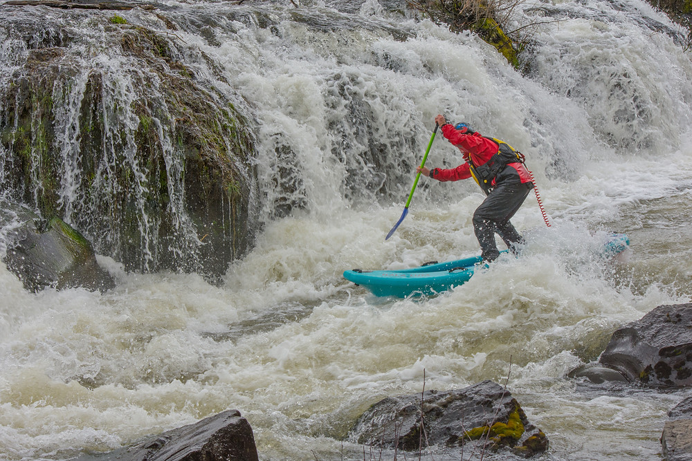 Awbrey Falls. Paul Clark whitewater paddle boarding on the Deschutes River.