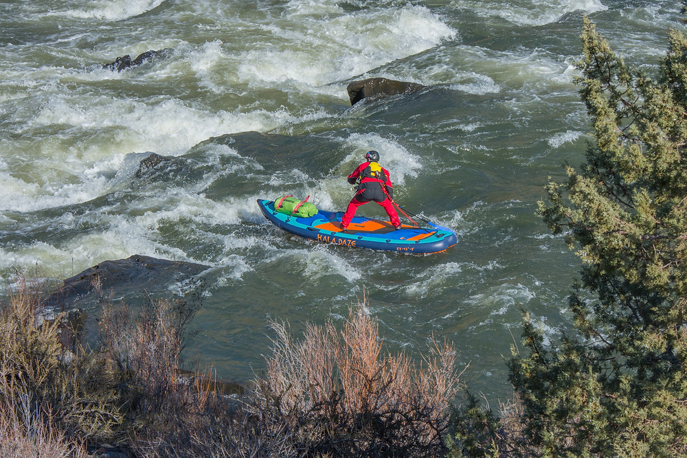 Paul Clark running the Clarno Rapids on a paddle board.
