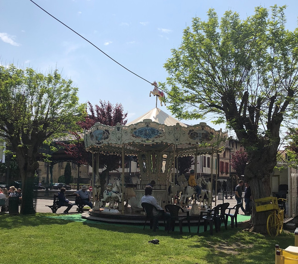 France, Mirepoix, village, weekly marketplace, shopping, vendors, local shopkeepers, carousel, merry go round
