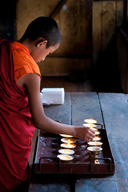 Young monk lighting candles