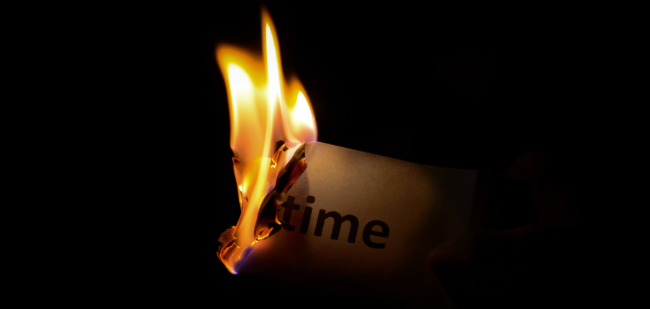 """Burning a piece of paper that says """"time."""""""