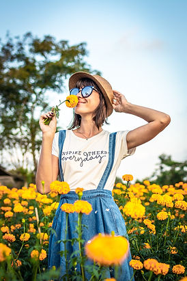 woman-holding-hat-and-smelling-yellow-flower-1832323.jpg