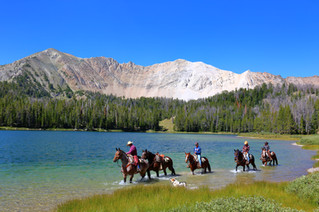 horseback riding in the mountains near a lake