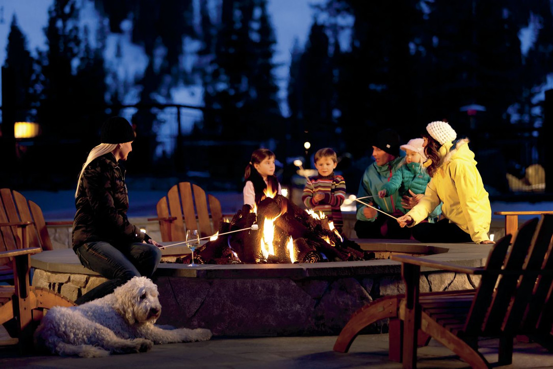 A group of people roasting marshmallows over a fire at a ski resort in tahoe