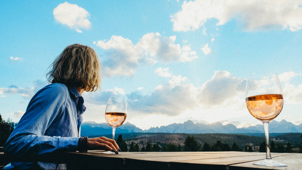 Woman enjoying a glass of wine at Idaho Rocky Mountain Ranch, view of rocky mountain range