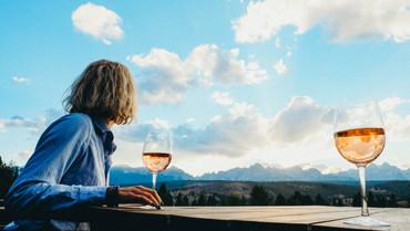 Woman enjoying a glass of wine at Idaho Rocky Mountain Ranch, view of rocky mountain range