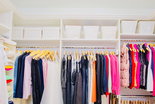Closet organization by Jenny Dietsch at Getting it Done Organizing | White closet with brightly colored clothing, canvas bins, and wooden hangers
