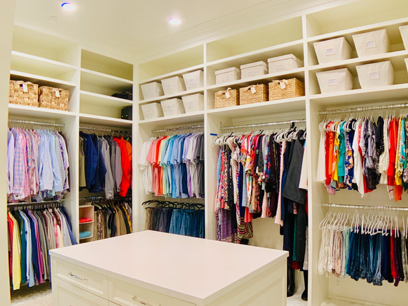 Closet organization by Jenny Dietsch at Getting it Done Organizing | White closet with brightly colored clothing, wicket baskets, canvas bins, and velvet hangers