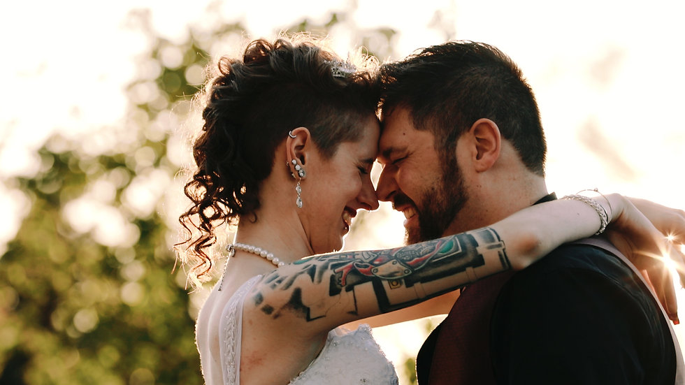 Allison and Jacob laugh, foreheads together as golden light breaks through the tree behind them