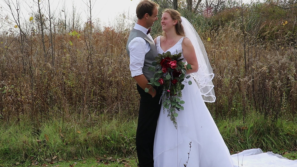 Susan and Matthias smile at each other in front of a field