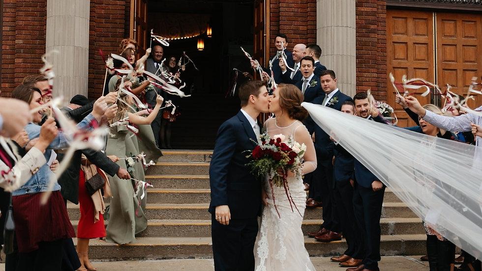 Kelsey (bride) and Blake (groom) kissing outside the steps of Sacred Heart of Jesus Catholic Church