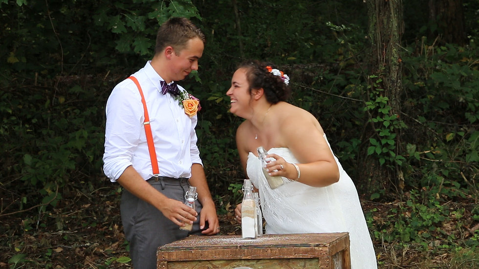 Derek and Damaris laugh together during their sand-combining ceremony