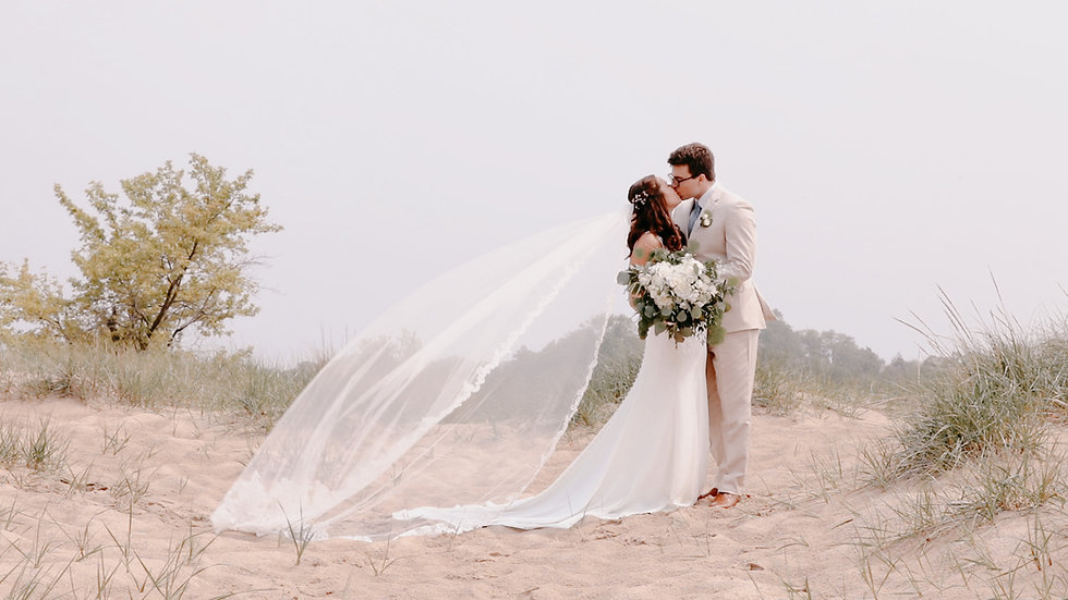 Stephanie and Alex kiss atop a dune at Holland State Park as Stephanie's veil blows in the wind