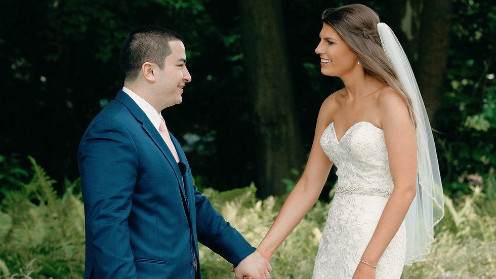 Annie and Kirk hold hands smiling at each other with the forest behind them at Ravines Golf Club