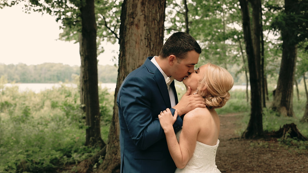Melissa and Rob kiss with the woods and lake behind them at their special place Van Buren Youth Camp