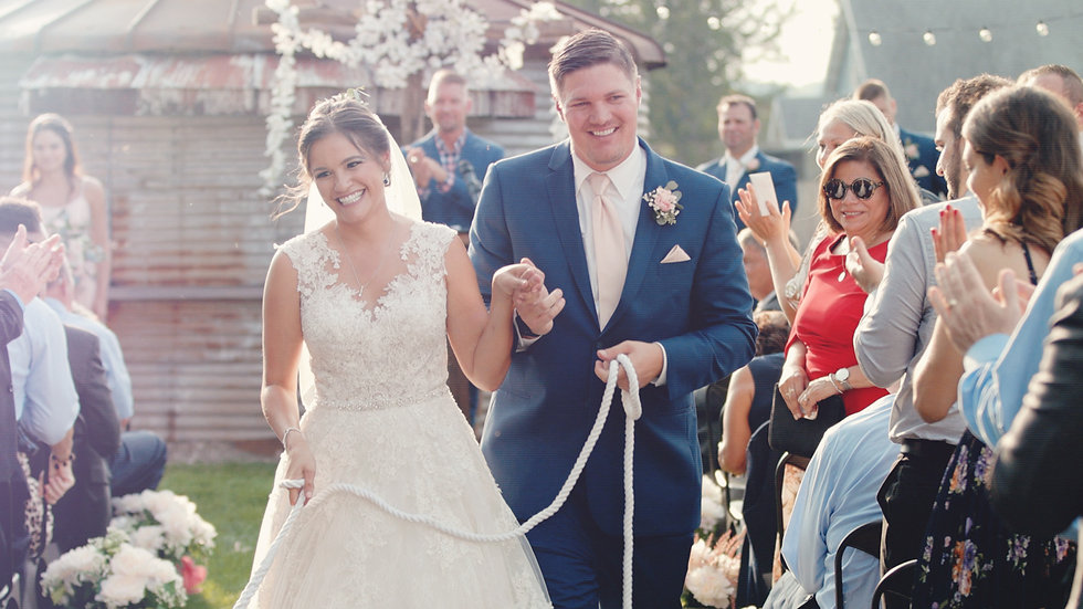 Danielle and Michael smiling as they exit their outdoor ceremony at Journeyman Distillery