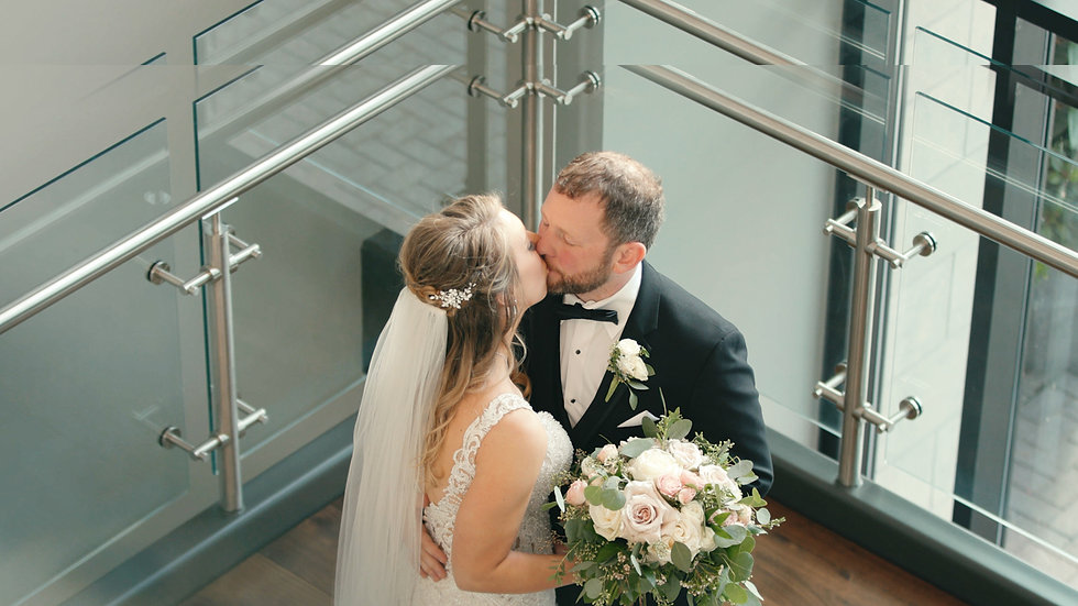 Lindsey and Chris kissing on the staircase of their reception location Embassy Suites Hotel