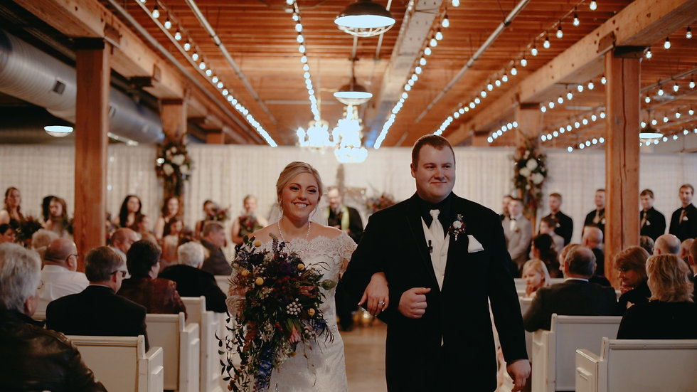 Molly and Dakota smile, coming down the isle from their ceremony inside The Cheney Place