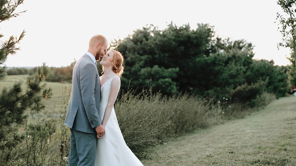 Rachael and Micah stand, noses touching as the sun sets behind them across the green fields