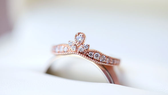 Women's rose gold wedding band with small diamonds resting atop men's rose gold wedding band.