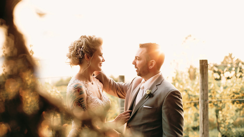 Nick brushes Amy's cheek as the sun streams behind them in the vineyard at Ciccone Vineyard & Winery