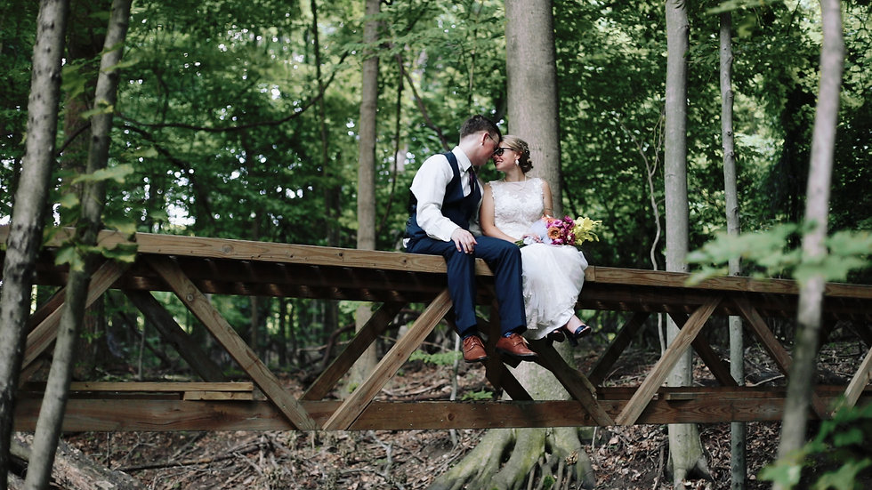 Emma and Ben sit atop a bridge in the woods, smiling at each other with their foreheads together