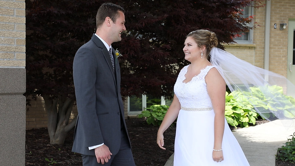 Hannah and Matt smile at each other during their first look outside the church