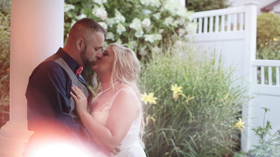 Casandra and Ryan kiss on the patio of Baypointe Inn