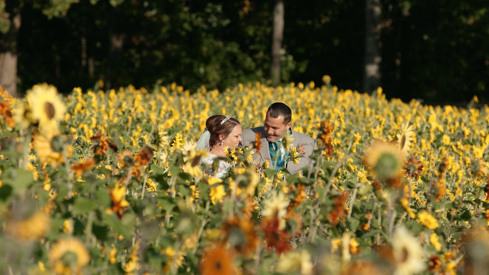 Andrea (bride) and Kevin (groom) laughing together in a field of sunflowers
