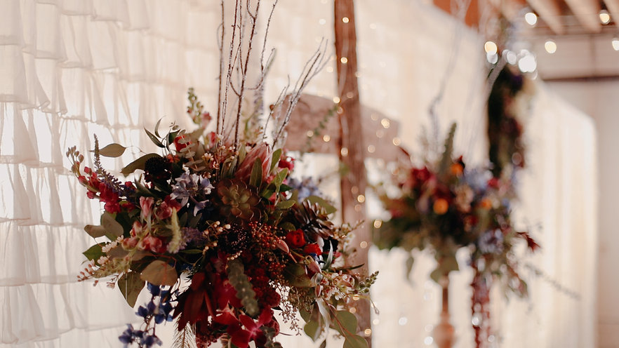 Two floral arrangements sit atop the alter, a cross in the background glitters with fairy lights