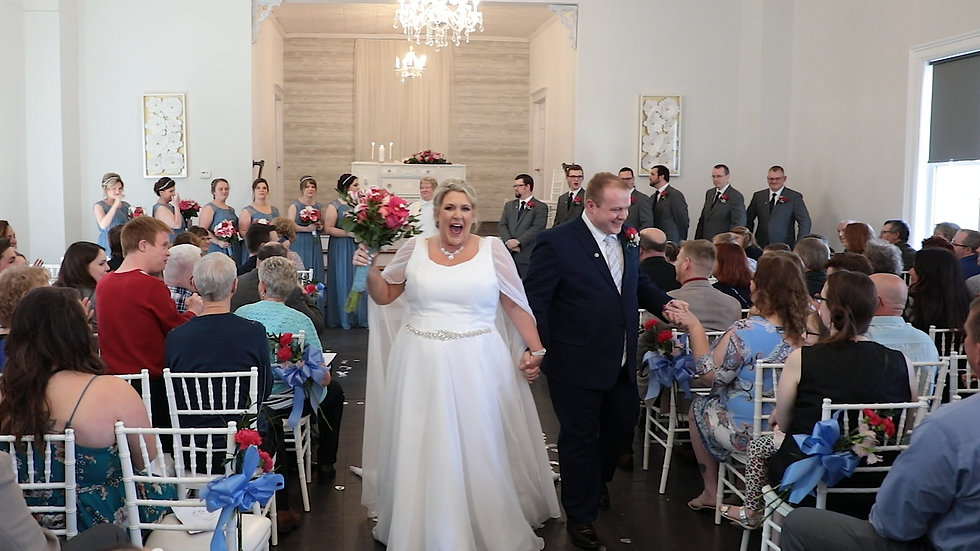 April and Dan exit down the isle with their friends and family smiling around them