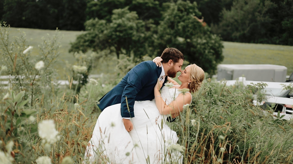 Drew dips Skyler for a kiss amid the flowers and grasses in the field outside the Hydrangea Blu Barn