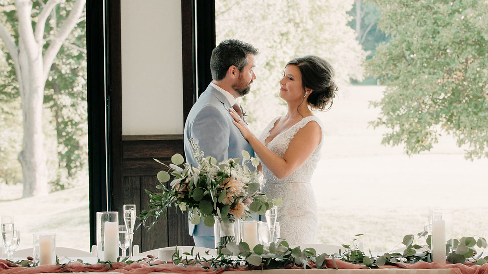Nicolie and Michael stare lovingly into each other's eyes at their head table at Railside Golf Club