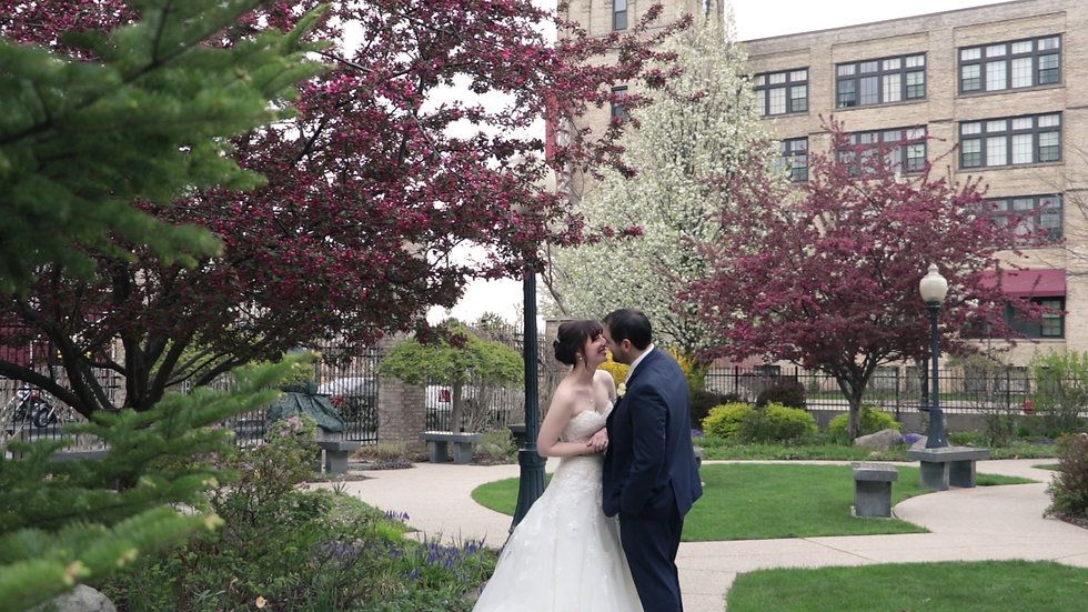 Rose and Ricardo stand smiling at each other amid a garden of flowering trees