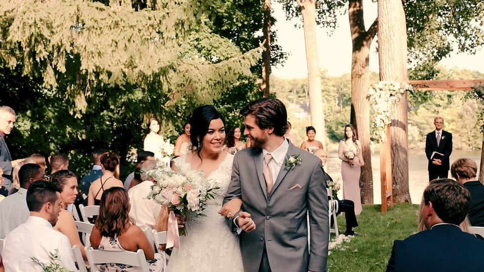 Stephanie and Ryan smile at each other, exiting down the isle from their outdoor ceremony
