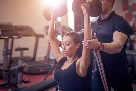 woman with dumbbells working on strength and conditioning with a personal trainer