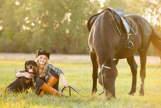 Girl horse rider sitting with a dog near