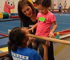 kids with coach in gymnastics class