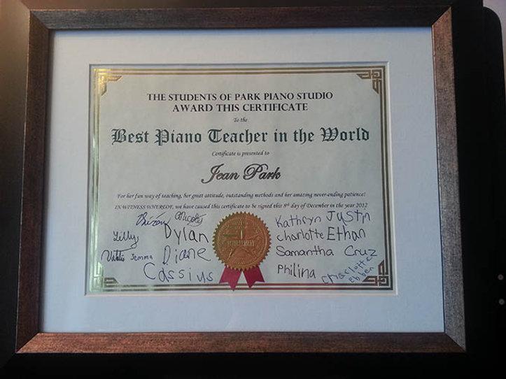 Students give piano teacher best piano teacher in the world certificate award