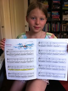 piano student holding music book with music piece